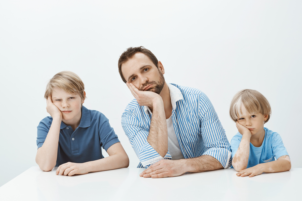 boys-feeling-bored-upset-portrait-tired-funny-european-family-sons-dad-sitting-table-leaning-heads-palms-staring-indifferent.jpg