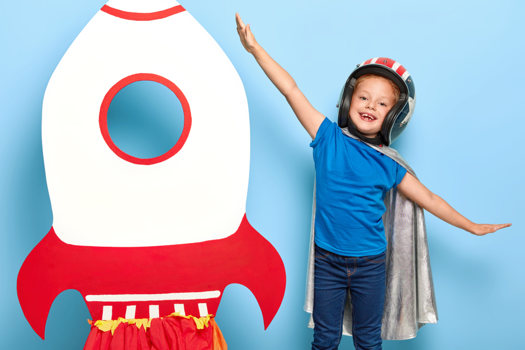 cute-happy-female-child-plays-astronaut-wears-flying-helmet-and-cape.jpg